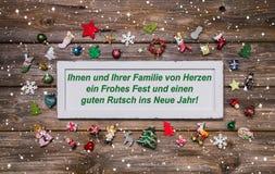 Cartolina di Natale con la decorazione variopinta ed il testo tedesco ch allegro Fotografia Stock