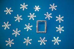 Cartolina di Natale con la struttura e fiocchi di neve su un fondo blu Fotografie Stock Libere da Diritti