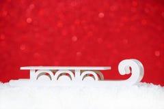 Cartolina di Natale con la vecchia slitta in neve, fondo rosso, spazio della copia Fotografia Stock Libera da Diritti
