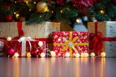 Cartolina di Natale con le decorazioni, i regali e le luci festivi sopra il copyspace variopinto del fondo immagine stock