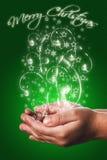 Cartolina di Natale con le mani di un bambino nel verde Fotografie Stock