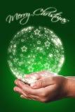 Cartolina di Natale con le mani di un bambino nel verde Immagini Stock