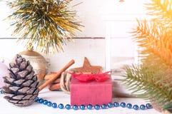 Cartolina di Natale con lume di candela, il contenitore di regalo ed il ramo dell'abete su fondo di legno immagini stock libere da diritti