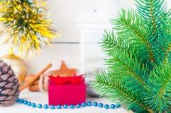 Cartolina di Natale con lume di candela, il contenitore di regalo ed il ramo dell'abete su fondo di legno immagini stock