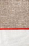 Cartolina di Natale con tela, nastro rosso su tela da imballaggio fotografia stock libera da diritti