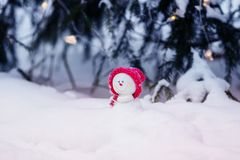 Cartolina di Natale con un pupazzo di neve sveglio festivo del giocattolo in un cappuccio rosa luminoso che si siede in un cumulo fotografia stock libera da diritti