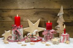 Cartolina di Natale decorata con le candele e le stelle rosse sulle sedere di legno Fotografia Stock Libera da Diritti