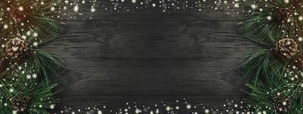 Cartolina di Natale Fondo di legno nero, con i rami del pino e le pigne da uno laterale, vista superiore Congratulazione di retta fotografia stock