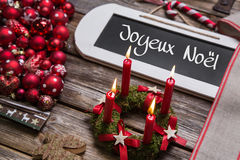 Cartolina di Natale francese con quattro candele brucianti rosse nel rosso Immagine Stock