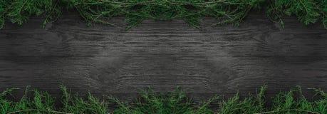 Cartolina di Natale Il fondo di legno nero con abete si ramifica su e giù, vista superiore Congratulazione di rettangolo di natal fotografie stock