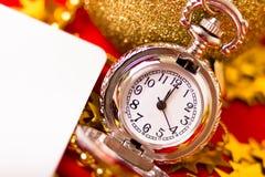 Cartolina di Natale L'orologio d'annata d'argento su un fondo rosso con va Fotografia Stock Libera da Diritti