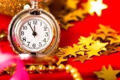 Cartolina di Natale L'orologio d'annata d'argento su un fondo rosso con va Fotografia Stock