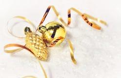 Cartolina di Natale palla dorata delle decorazioni di natale, pinecone, nastro dorato su un fondo bianco con neve e luci morbide fotografia stock