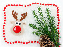 Cartolina di Natale rossa e bianca, renna, christmastree, pigna, ghirlanda in neve Fotografia Stock
