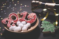 Cartolina di Natale: su un piatto di legno sono i biscotti dello zenzero rosso sotto forma dei numeri 2019 e fiocchi di neve roto fotografia stock libera da diritti