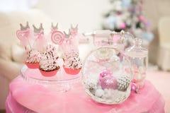 Cartolina di Natale, tavola rosa dolce con i coni dei dolci, su un fondo dell'albero di Natale Fotografia Stock