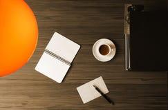 Cartolina, penna, libri e caffè in bianco sullo scrittorio, illuminato da una lampada da tavolo fotografia stock