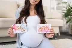 Cartoline d'auguri della tenuta della donna incinta Fotografia Stock