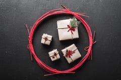 Cartoline d'auguri di giorno del ` s del nuovo anno e di Natale, vacanze invernali in un cerchio rosso, regali neri del fondo Fotografia Stock Libera da Diritti
