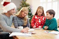 Cartoline di Natale di scrittura della famiglia insieme Fotografie Stock