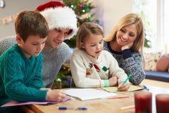Cartoline di Natale di scrittura della famiglia insieme Fotografie Stock Libere da Diritti