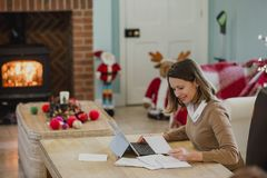 Cartoline di Natale di scrittura della donna a casa Immagine Stock