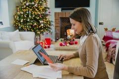 Cartoline di Natale di scrittura della donna a casa Fotografia Stock