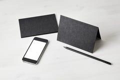 Cartoline e telefono cellulare di carta neri sulla tavola di legno cancelleria Spazio per la disposizione di progettazione Immagine Stock Libera da Diritti