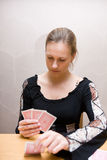 The cartomancy. Young beautiful girl sitting at the table reading cards Stock Photography