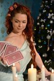 Cartomancy on Christmas Eve. Woman with cards on Christmas Eve Royalty Free Stock Images