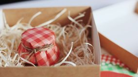 Carton box with Christmas jam. Colorful decoration of Christmas gift. Homemade present for New Year holidays stock video