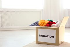 Carton box with donations on floor indoors. Space for text royalty free stock photo