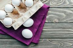 Carton box with white eggs. On purple napkin stock photos