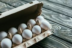 Carton box with white eggs. On wooden table royalty free stock images
