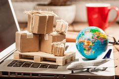 Carton boxes on computer as online shopping logistics concept. Global logistics concept with online trading and shopping in the internet, packages to be Royalty Free Stock Image