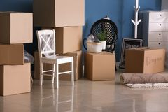 Carton boxes and interior items on floor in room. Moving house concept royalty free stock photography