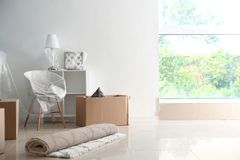 Carton boxes and interior items on floor in room. Moving house concept stock photos