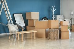 Carton boxes and interior items on floor in room. Moving house concept stock photography