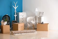Carton boxes and interior items on floor in room. Moving house concept royalty free stock photos