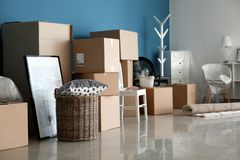 Carton boxes and interior items on floor in room. Moving house concept stock photo