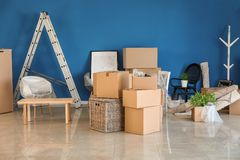 Carton boxes and interior items on floor in room. Moving house concept royalty free stock photo
