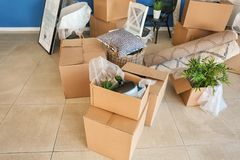 Carton boxes and interior items on floor in room. Moving house concept royalty free stock images
