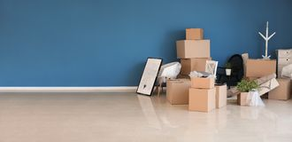 Carton boxes and interior items prepared for moving into new house near color wall stock photo