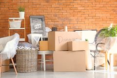 Carton boxes and interior items in room. Moving house concept royalty free stock images