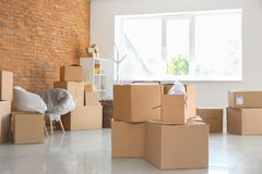 Carton boxes and interior items in room. Moving house concept royalty free stock photo