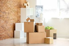 Carton boxes and interior items in room. Moving house concept royalty free stock photos