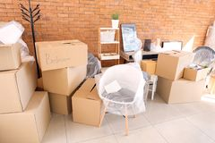 Carton boxes and interior items in room. Moving house concept stock photos