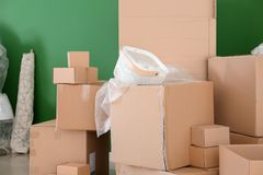 Carton boxes and interior items in room. Moving house concept stock photography