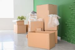 Carton boxes and interior items in room. Moving house concept stock image