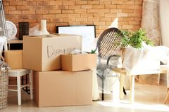 Carton boxes and interior items in room. Moving house concept royalty free stock image